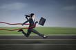 Happy businesswoman crossing finish line