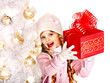 Child in hat  holding red  gift box near white Christmas tree.