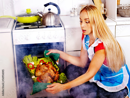 Woman cooking chicken at kitchen.