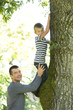 Father holding son while he climbs a tree