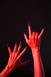 Red devil hands with long black nails, real body-art