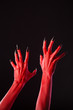 Red devil hands with sharp black nails, real body-art