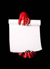 Red devil hands with black nails holding blank paper scroll