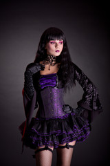 Romantic witch in purple and black gothic Halloween outfit