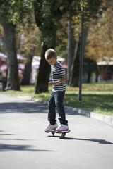 Young boy skateboarding in street