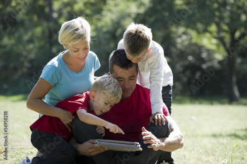 Young family looking at tablet computer in the park