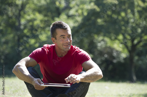 Man sitting park with a tablet computer