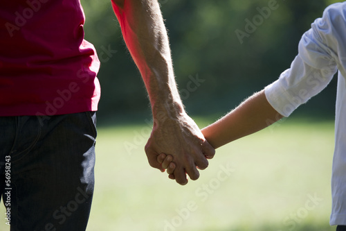 Father and young son holding hands