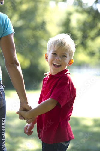 Young boy holding his mother's hand