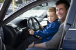 Father letting son sit in the driving seat of a car