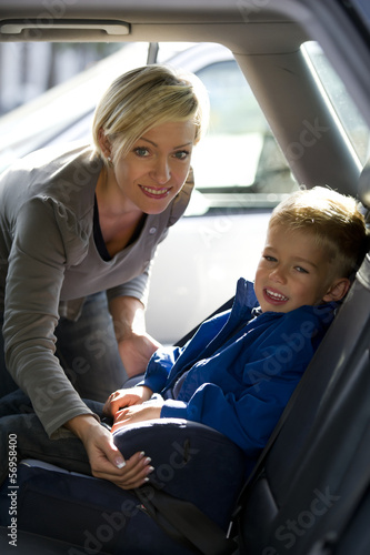 Mother putting son in car seat.