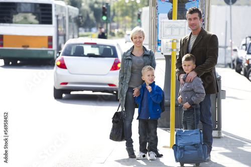 Family in city street with bags