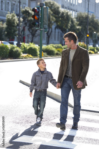 Father and son walking across street