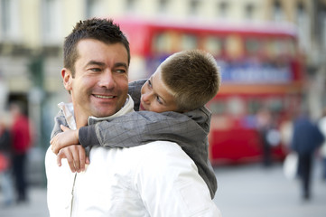 Father holding son walking in London street