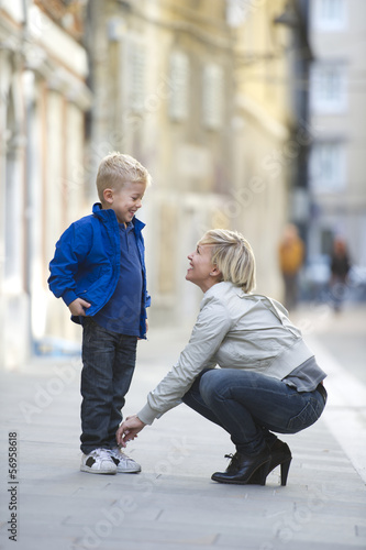 Mother tying son's shoestring.