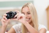 lächelnde blonde frau schaut auf digitalkamera