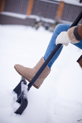 Women's feet at winter boots on snow shovel
