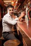 portrait of handsome man sitting in bar and holding glass
