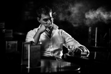 Black and white portrait of man smoking cigarette in restaurant