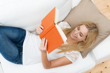 lächelnde blonde frau liest ein buch