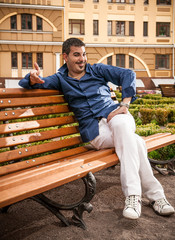 Macho man sitting on bench in park