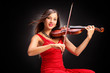 Young attractive woman in red dress playing the violin