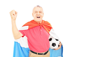 Senior male sport fan, with dutch flag holding a ball