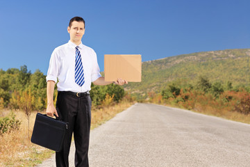 Young businessman holding a leather suitcase and hitchhiking