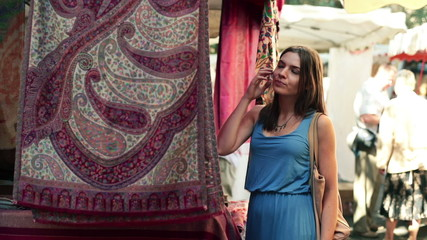 Woman looking at beautiful carpet at city market