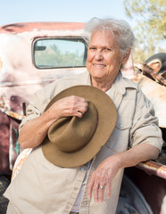 Smiling lady with a hat leaning against a vintage truck