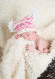 Beautiful newborn baby wearing a pink hat with white pom poms