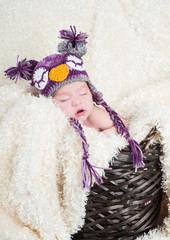 Sleeping baby in a basket wearing a crocheted owl hat