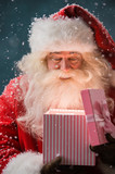 Portrait of happy Santa Claus opening gift box