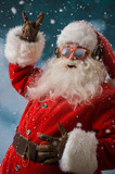 Fototapety Santa Claus is listening to music in headphones outdoors at Nort