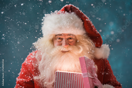 Happy Santa Claus opening his Christmas gift at North Pole