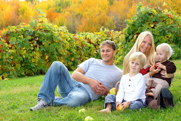 Happy Family Sitting in the Grass Eating Apples at Orchard