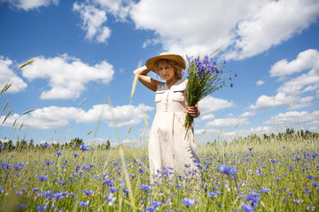 Happy woman in corn field with cornflowers