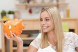 blonde junge frau schaut lächelnd auf ihr sparschwein