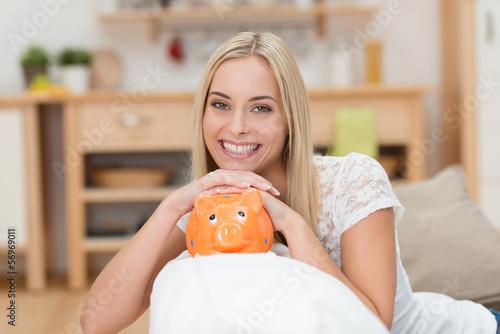 lachende junge frau stützt kinn auf sparschwein