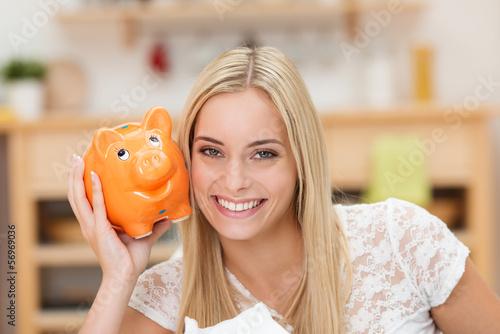 glückliche studentin mit sparschwein in ihrer wohnung