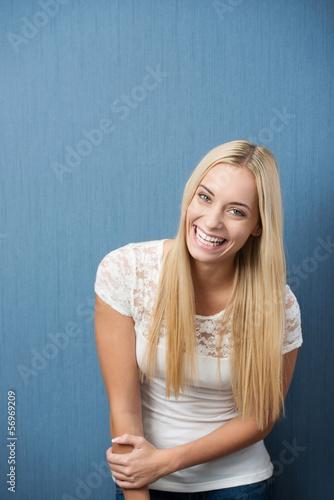 junge lachende frau vor grauer wand