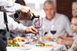 Kellner gießt Wein in ein Glas
