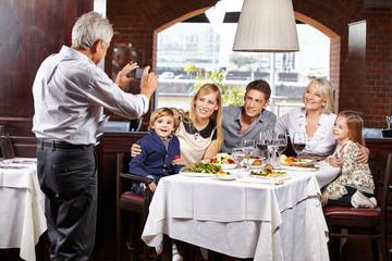 Opa macht Familienfoto mit Smartphone