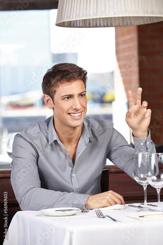 Mann im Restaurant ruft den Kellner