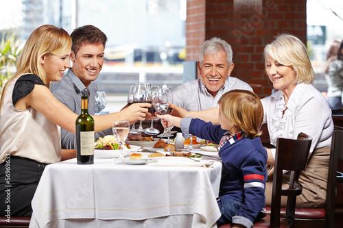 canvas print picture Familie im Restaurant prostet sich zu