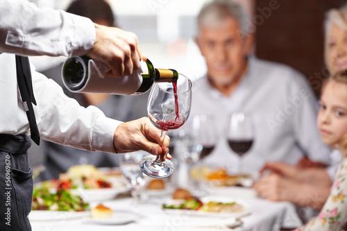 Kellner gießt Wein in ein Glas - 56969670