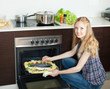 Positive housewife cooking raw fish in oven