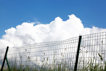 Blauer Himmel und Wolken am Zaun