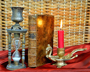 Magic book, firing candle and hourglass