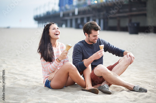 couple sitting in sand at sant monica pier.